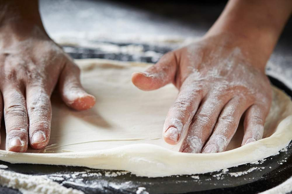 two hands making pizza dough