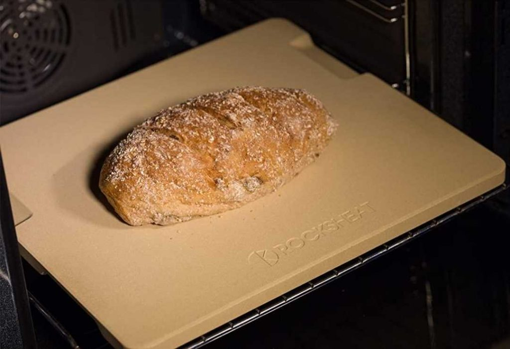 A square baking stone with a loaf of bread on it.