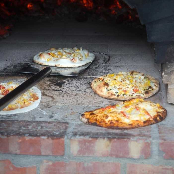 A professional pizza oven with multiple pizzas baking inside.
